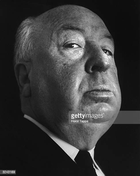 Lowangle headshot portrait of British film director Alfred Hitchcock against a dark backdrop