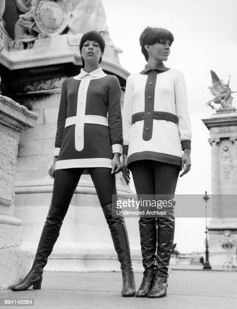 Low-angle portrait of a pair of unidentified models, dressed in thigh-high boots and inversely matching mini dresses, 1969.