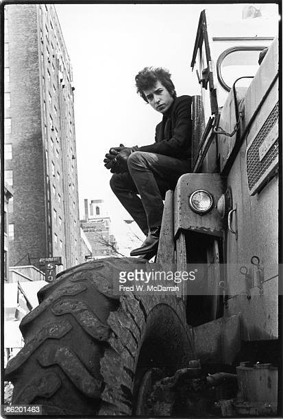 Lowangle portrait of American musician Bob Dylan as he perches the cab of a bulldozer in Sheridan Square Park New York New York January 22 1965