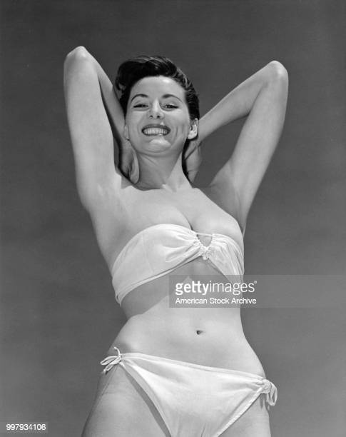 Lowangle portrait of an unidentified model in a strapless twopiece bathing suit as she poses with her arms behind her head Los Angeles California...