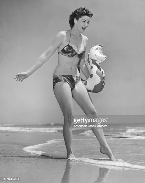 Lowangle portrait of an unidentified model in a twopiece bathing suit as she holds an inflatable seahorse under one arm and dips toes in the surf at...