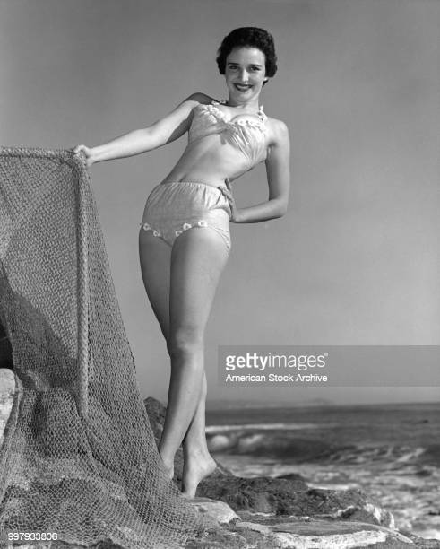 Lowangle portrait of an unidentified model in a twopiece bathing suit as she poses one hand on a fishing net at the beach Los Angeles California...