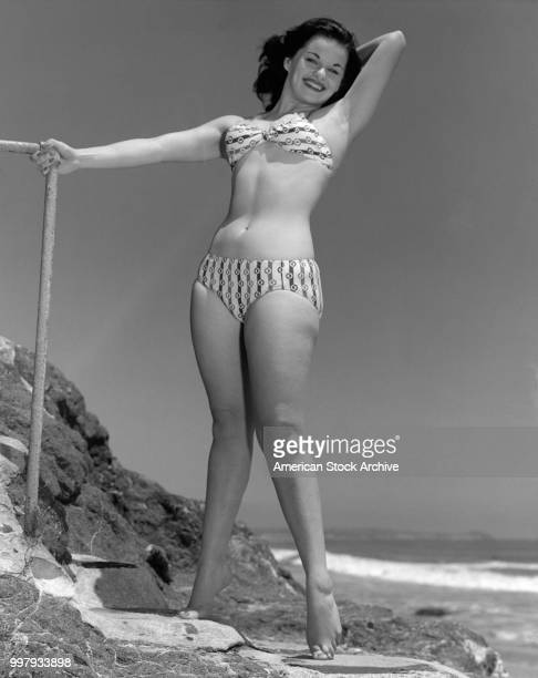 Lowangle portrait of an unidentified model in a twopiece bathing suit as she poses on a rocky outcrop at the beach Los Angeles California January 25...