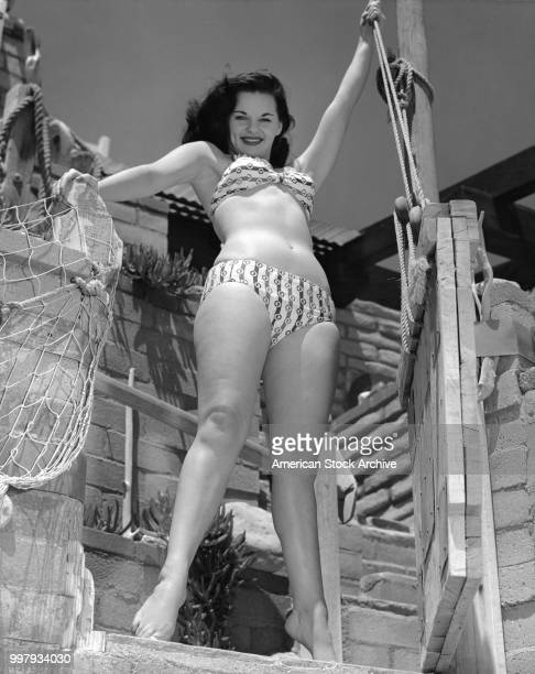 Lowangle portrait of an unidentified model in a twopiece bathing suit as she poses on a wooden structure draped with a fish net Los Angeles...