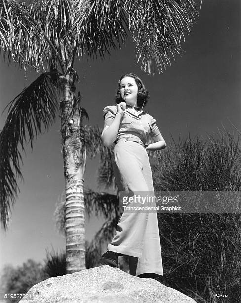 Lowangle portrait of Canadianborn American actress and model Deanna Durbin as she poses atop a rock circa 1950