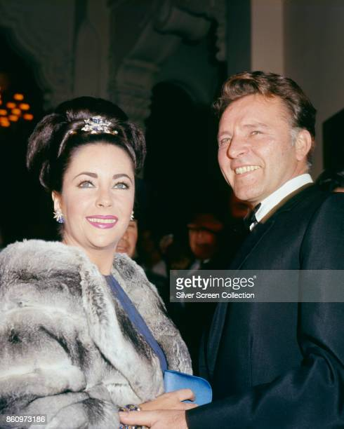 Lowangle portrait of married actors Elizabeth Taylor and Richard Burton as they attend the premiere of the latter's film 'The Spy Who Came in from...