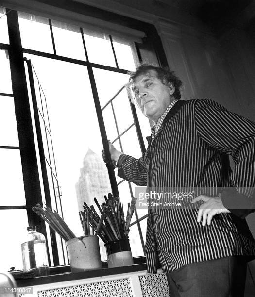 Low-angle portrait of Russian-born French artist Marc Chagall as he stands next to an open window, New York, New York, 1945.