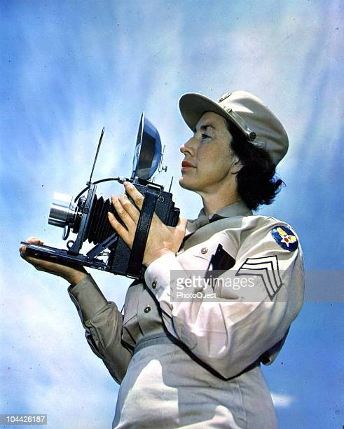 Low-angle profile portrait of an unidentified Women's Army Corps sergeant as she holds a still camera , March 6, 1946.