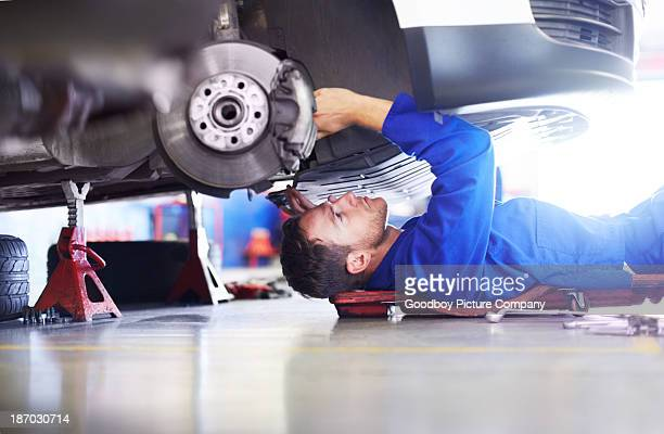 Low-angle shot of mechanic working under a car