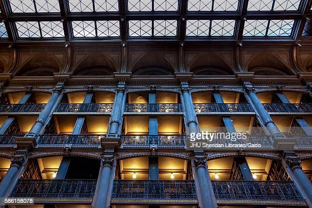 Low-angle shot of the levels of the George Peabody Library, a research library for Johns Hopkins University, with cast iron railings and exposed...