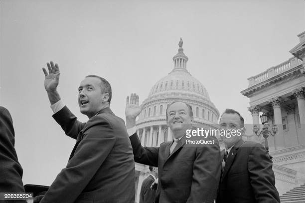 Lowangle view near the US Capitol of American politician US Vice President Hubert H Humphrey and astronauts James McDivitt Edward White II ride in a...