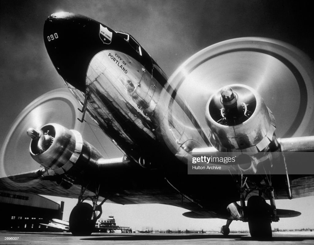 Low-angle view of a Douglas DC 3 airliner 'City of Portland,' with its propellers spinning in preparation for take off from an airport runway. These aircraft were a mainstay of early commercial aviation in the postwar era.