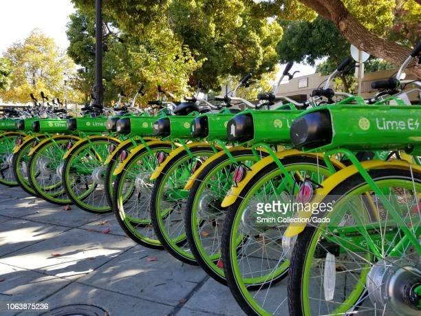 Lowangle view of a long row of green and yellow bicycles from sharing economy company Lime in the Silicon Valley town of Mountain View California...
