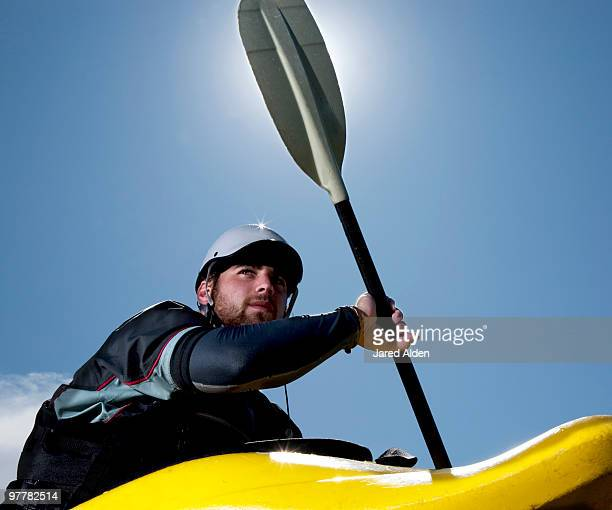 low-angle view of a male kayaker in a playboat is backlit by the sun. - canoe stock pictures, royalty-free photos & images