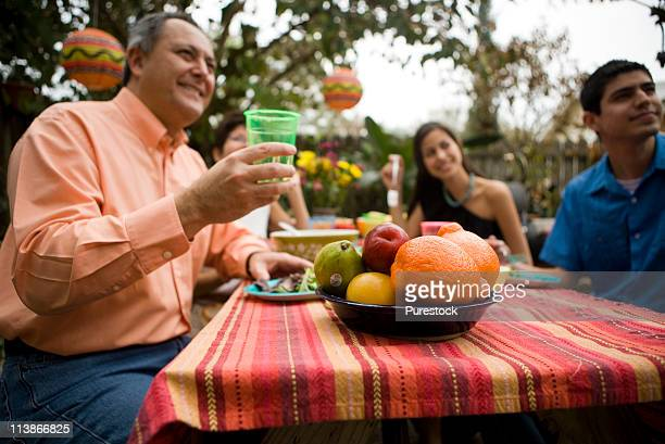 Low-angle view of a smiling family having a meal at a picnic table