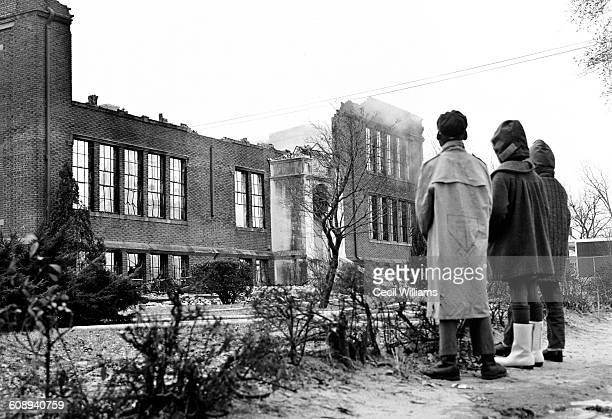 Lowangle view of a trio of students as they stand in front of the still smoking remains of the Dunton Memorial School on Goff Avenue after a fire...
