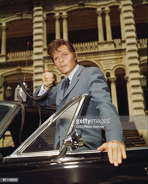 Lowangle view of American actor Jack Lord in character as Detective Steve McGarrett speaks on a portable radio in a scene from an episode of the...