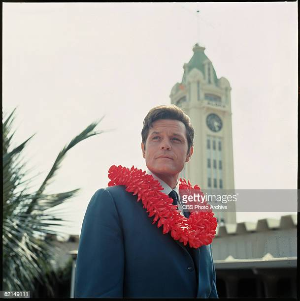 Lowangle view of American actor Jack Lord in character as Steve McGarrett as he stands with a lei around his neck in a scene from the television...