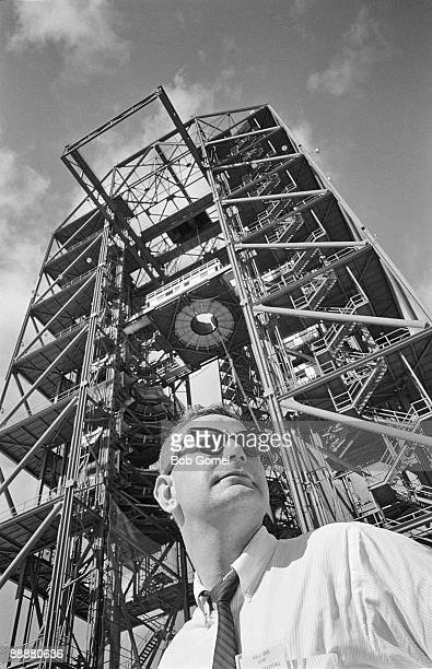 Low-angle view of American astronaut John Glenn as he stands, framed against the construction platform for one of the rockets scheduled to be used in...