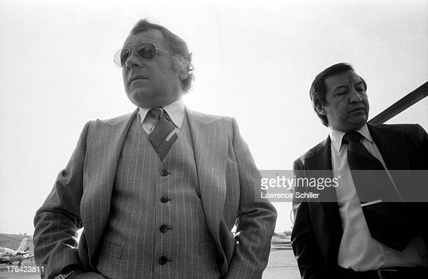Lowangle view of American attorney F Lee Bailey and an unidentified man as they stand on the tarmac at an unidentified airfield in San Francisco...