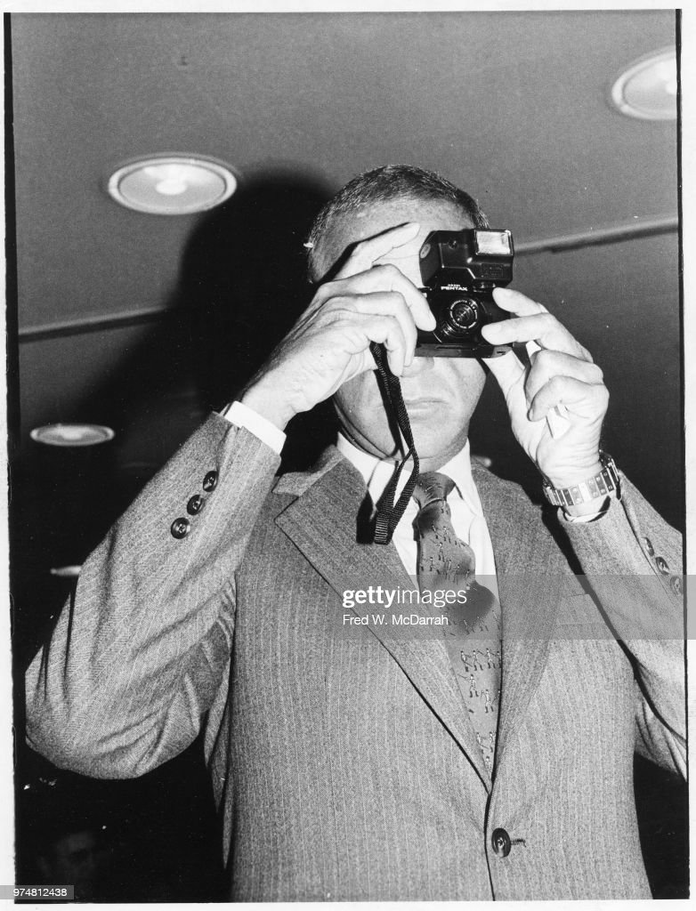 Low-angle view of American attorney Roy Cohn (1927 - 1986) as he takes a photograph at a Friar's Club Roast, New York, New York, July 21, 1977.