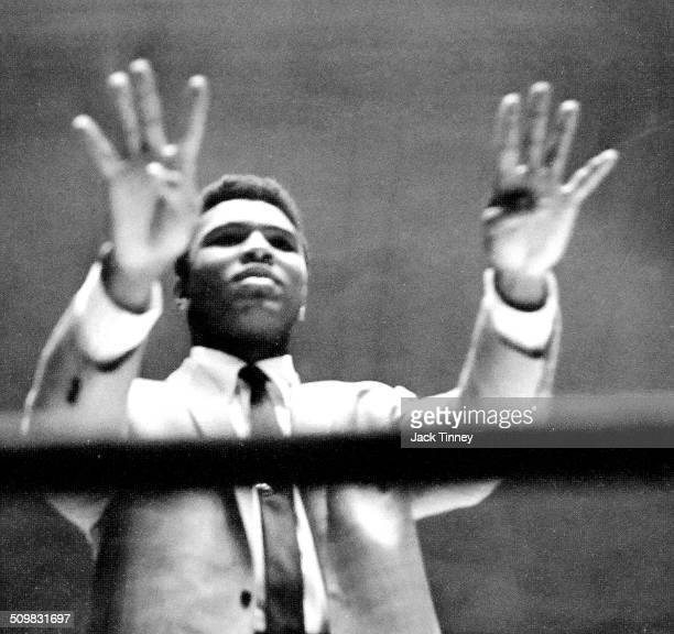 Lowangle view of American heavyweight boxer Muhammad Ali as he holds upholds up eight fingers in in the ring at Convention Hall Philadelphia...