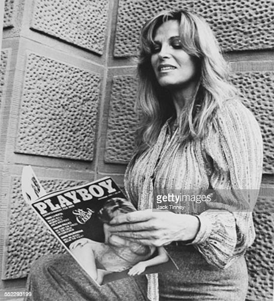 Lowangle view of American model Vikki LaMotta as she holds open the November 1981 issue of Playboy magazine in which she posed Philadelphia...