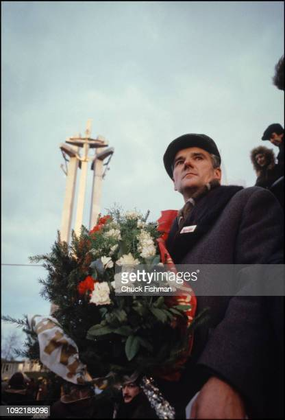 Lowangle view of an unidentified man with a Solidarnosc trade union pin on his coat and a bouquet of flowers as he stands near the entrance to the...