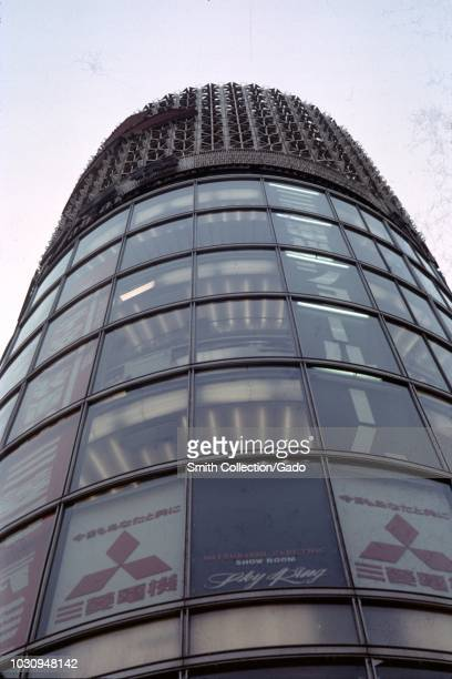 Low-angle view of building with logo for Japanese conglomerate Mitsubishi and sign in English reading Mitsubishi Electric Show Room, Sky King, in...