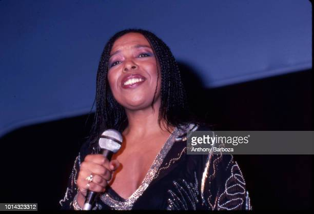 Lowangle view of Jazz and RB musician Roberta Flack as she holds a microphone and smiles onstage late twentieth century
