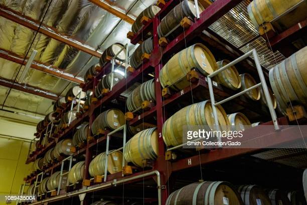 Lowangle view of large number of wooden wine barrels on racks used for the long term aging of wines at a wine production facility in Sonoma County...