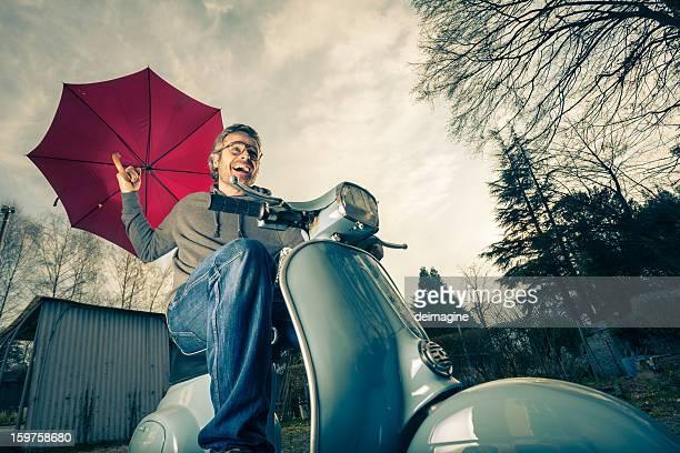 vue de bas-angle élevé d'homme sur un scooter rouge parapluie - moto humour photos et images de collection