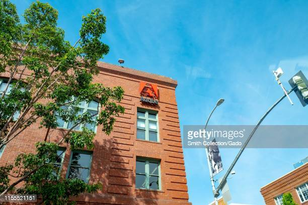 Low-angle view of sign with logo on facade at office of computer software company Adobe in the South of Market neighborhood of San Francisco,...