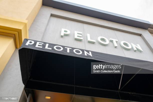 Low-angle view of sign with logo on facade at Peloton upscale spin cycle retail store in Walnut Creek, California, December 17, 2019.
