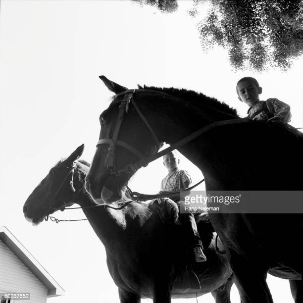 Low-angle view of two boys as they sit atrid horses, Mulchen, Biobio, Chile, November 1960.