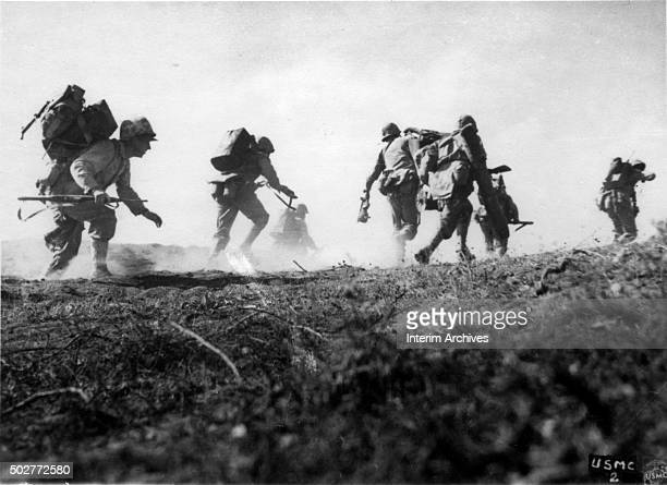 Lowangle view of US Marines carrying packs and equipment as they crouch and run towards the cover of smoke during the inland drive Iwo Jima Japan 1945