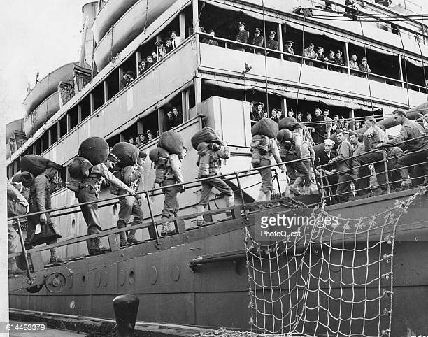 Lowangle view of US soldiers as they carry their belongings across the gangplank as they board the USS Republic Fort Mason California June 7 1942