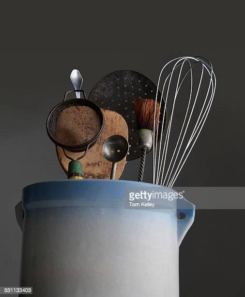 Lowangle view of various kitchen tools among them a whisk a strainer and a brush inside a crock container 2008