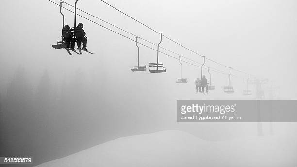 Low-Angle View Of Young Couple On Ski Lift