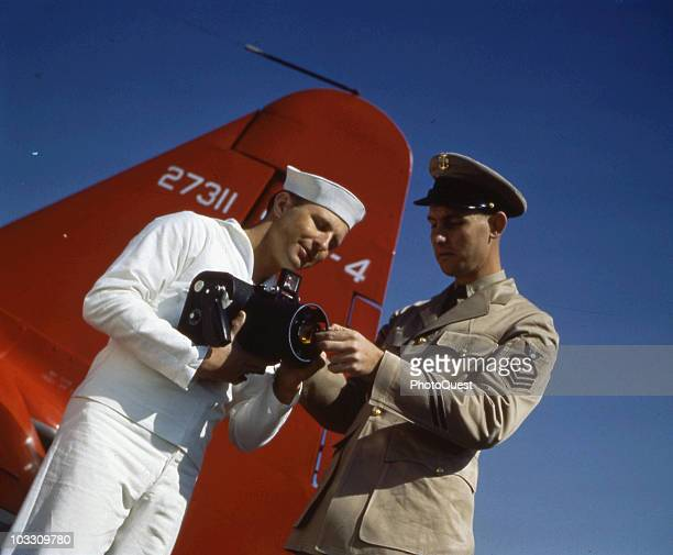 Lowangled canted view of a Chief Photographer's Mate as he instructs an aerial photography student in the use of a handheld aerial camera Pensacola...