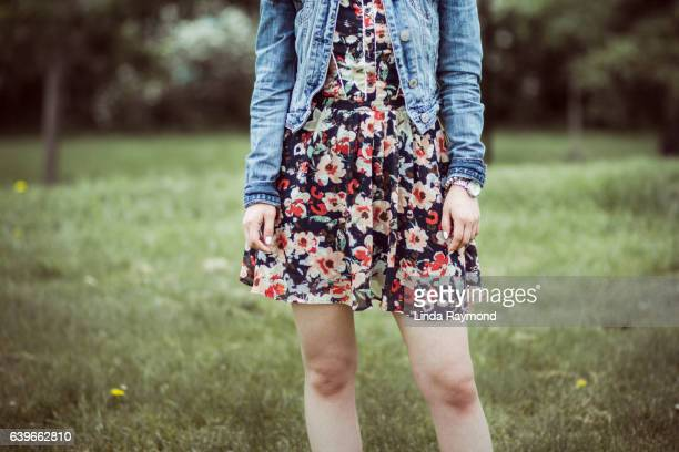 Lower body of a girl with a floral dress and a jeans coat