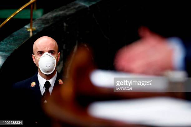 Lower Chamber's usher protected with a mask attends the plenary session at Lower Chamber of Spanish Parliament, in Madrid on 09 April 2020 during a...