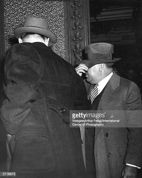 Lower East Side gangster and bootleg liquor distributor Irving Wexler, known as Waxy Gordon, pulls his hat down over his face to hide from the camera.
