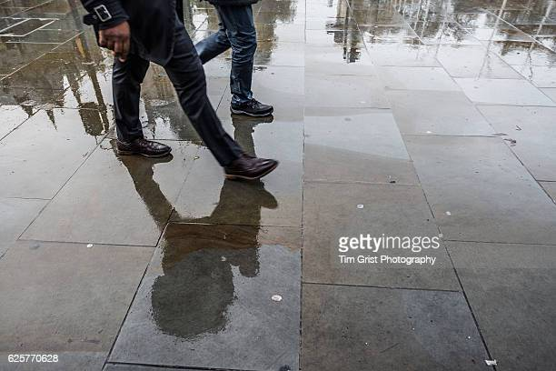 Lower half of Two Commuters Walking on a Wet  Pavement, London