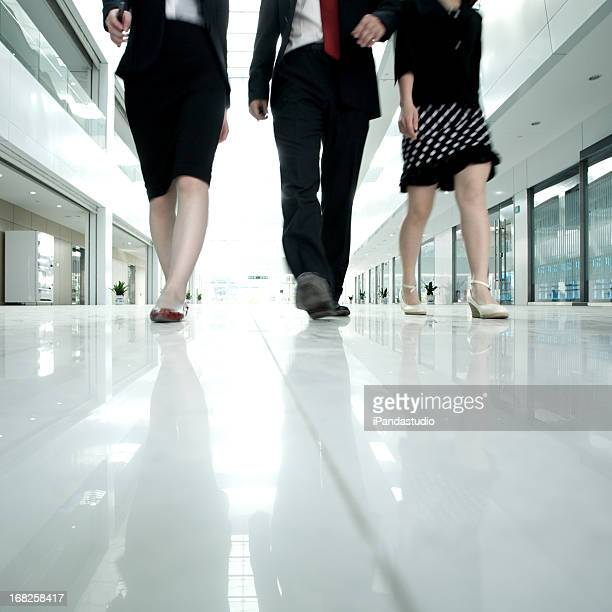 Lower half photo of business people walking in white hall