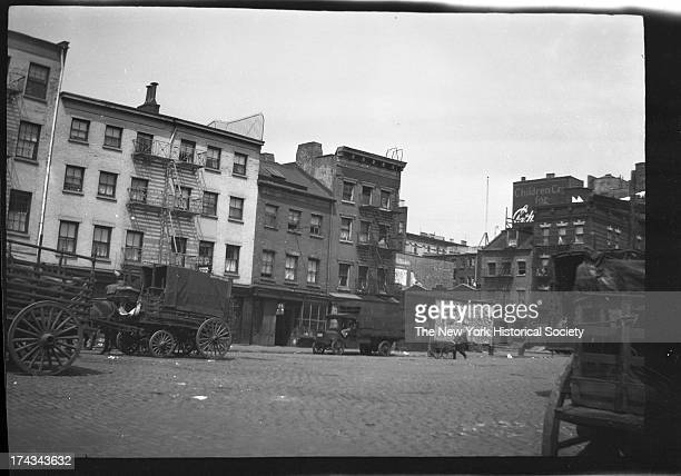 Catherine Street west of South Street, cobbled street with horse-drawn delivery carts , New York, New York, mid 1920s.