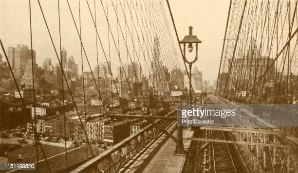 """Lower Manhattan Viewed Through The Network Of Cables On Brooklyn Suspension Bridge', circa 1930. From """"The Wonder Book of Engineering Wonders"""",..."""