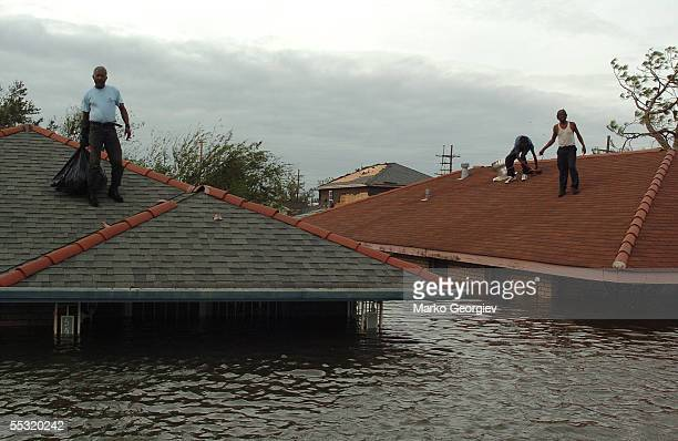 Lower Ninth Ward residents stranded on the roofs wait for a rescue boats in New Orleans, Louisiana on August 29, 2005. Hurricane Katrina slammed...
