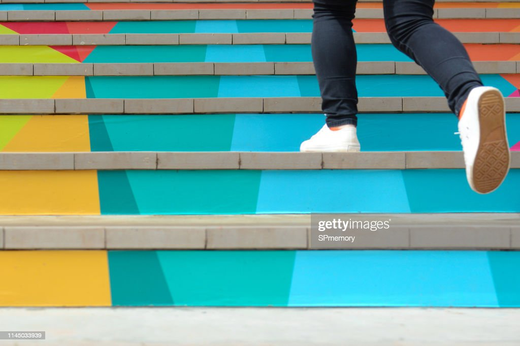 Lower part of teenage girl in casual shoe walking up outdoor colorful stair,teenage lifestyle successful concept : Stock Photo