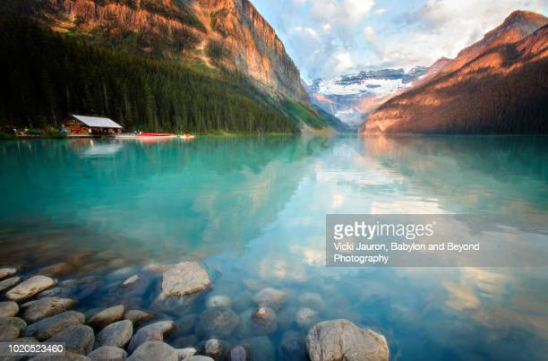 lower perspective view of sunrise and turquoise colors at lake louise - teal stock pictures, royalty-free photos & images